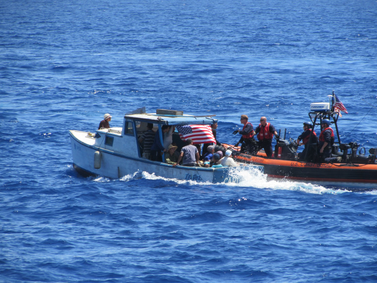 A Coast Guard boatcrew pulls alongside a vessel carrying Cuban migrants off the coast of Florida. The migrants were safely removed from the rustic vessel and repatriated to Cuba.