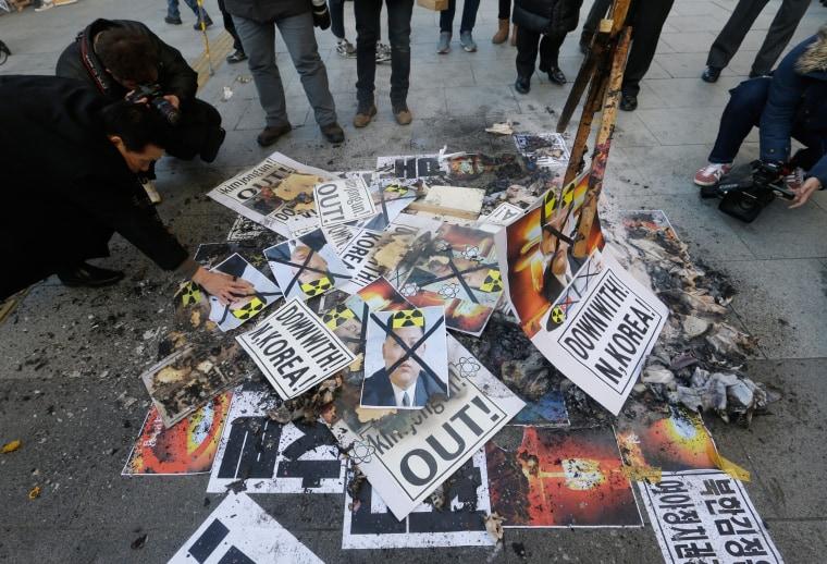 Image: A protester displays defaced photos of North Korean leader Kim Jong Un