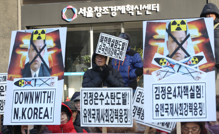 Image: Protesters with defaced photos of Kim Jong Un are seen