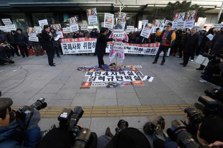 Image: A protester prepares to burn an effigy of the North Korean leader