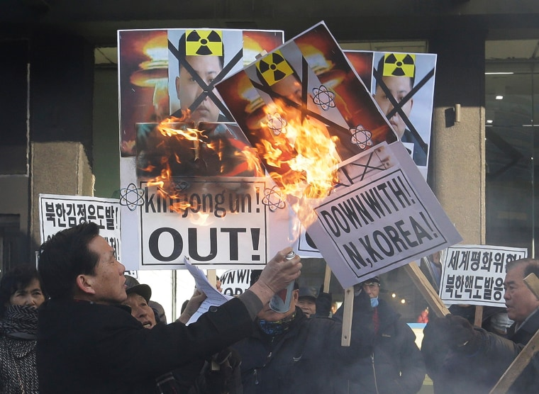 Image: A protester burns the defaced pictures of Kim Jong Un