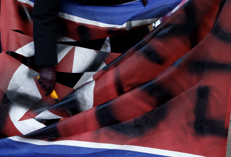 Image: Activists tear a North Korean flag