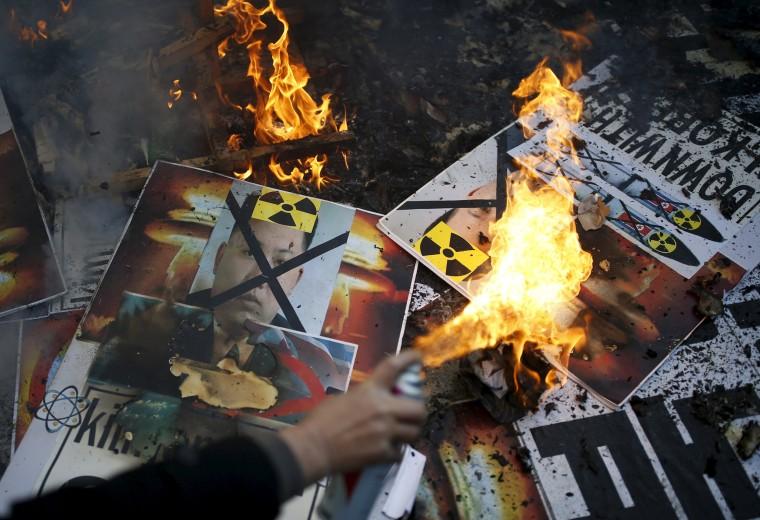 Image: A protester burns banners depicting Kim Jong Un