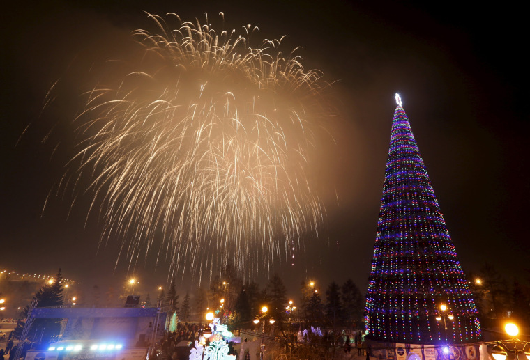 Image: Fireworks explode behind Christmas tree during Orthodox Christmas celebrations in the Siberian city of Krasnoyarsk