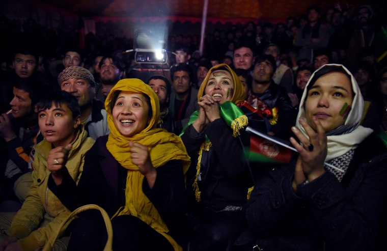 Image: Afghan soccer fans cheer for their national team as they watch a live broadcast of the SAFF Championship match
