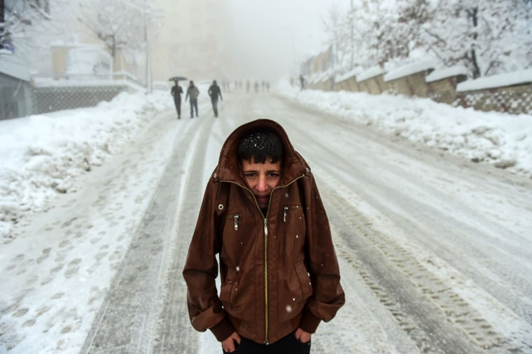 Image: A Kurdish boy protects himself against the cold as heavy snow hits the city of Sirnak