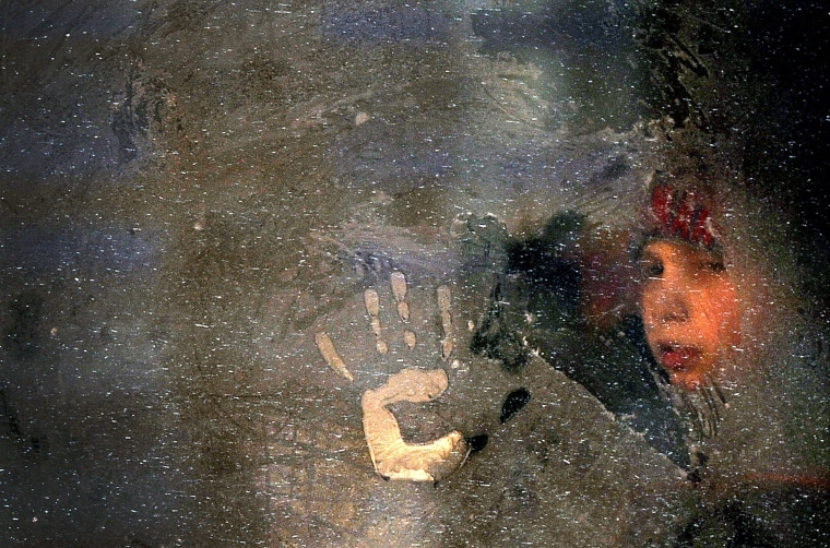 Image: A boy looks through a frozen bus window in Minsk, Belarus