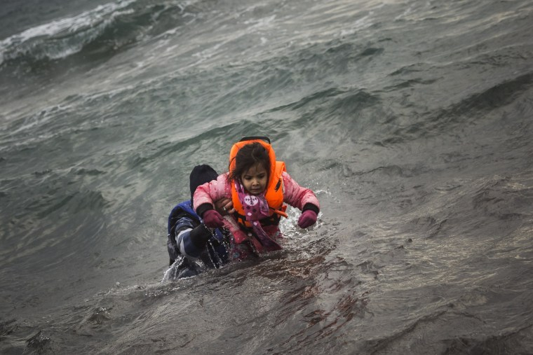 Image: A man carries a child as they try to reach the shore on the Greek island of Lesbos