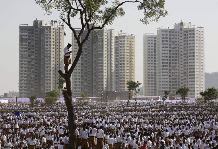 Image: A volunteer of the Hindu nationalist organisation Rashtriya Swayamsevak Sangh stands on a tree