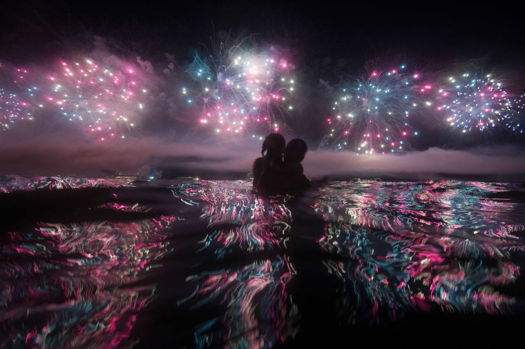 Image: A couple watches fireworks just after New Years at Copacabana beach