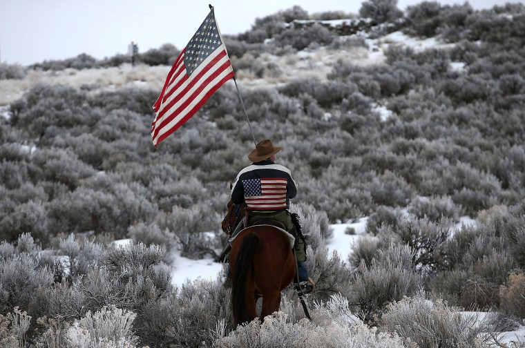 Image: Dwayne Ehmer carries an American flag as he rides his horse on the Malheur National Wildlife Refuge