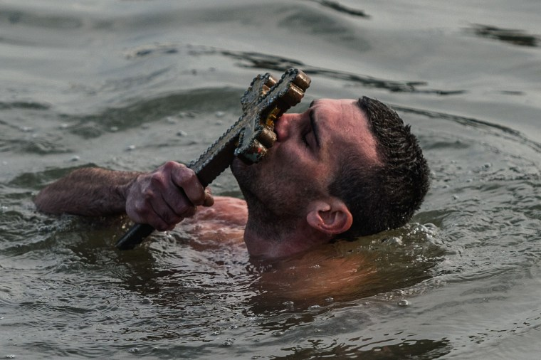 Image: Greek Orthodox swimmer Nicolaos Solis kisses a wooden cross retrieved from the Bosphorus river