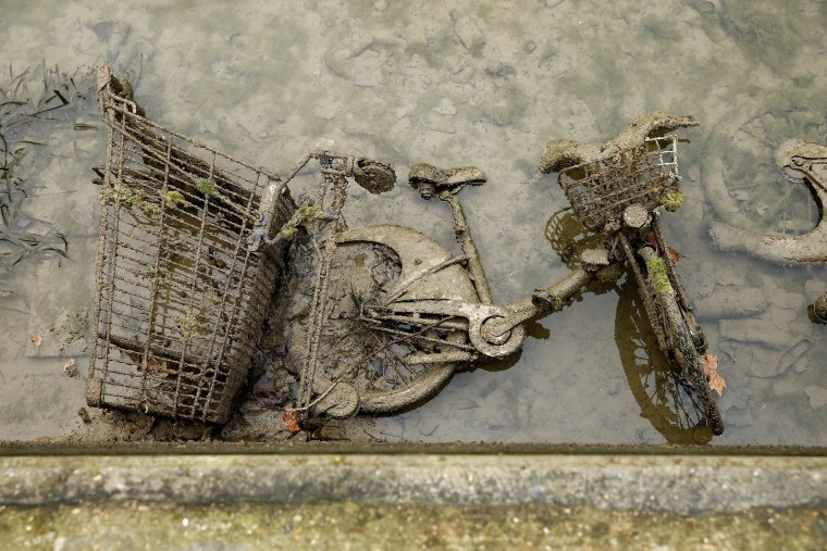 Image: A bicycle and a shopping cart covered with mud appear after the canal Saint-Martin was drained
