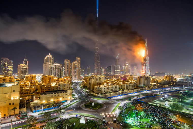 Image: Flames and smoke billow from a building after a fire broke out at the The Address Hotel in Dubai