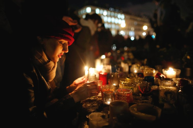 Image: People gather on the Place de la Republique square to pay tribute to the victims of last year's shooting at the French satirical newspaper Charlie Hebdo in Paris