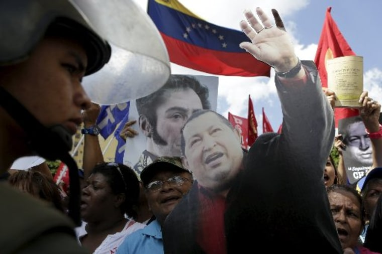 Supporters of Venezuela's President Nicolas Maduro gather outside Supreme Court building next to a cardboard cut-out of Venezuela's late President Hugo Chavez in Caracas, January 7, 2016.