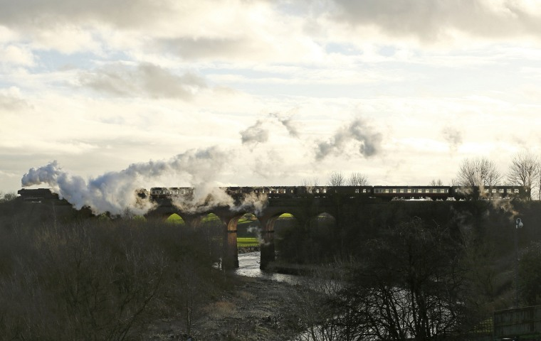 Image: The Flying Scotsman steam engine passes over a viaduct as it leaves East Lancashire Railway in Bury