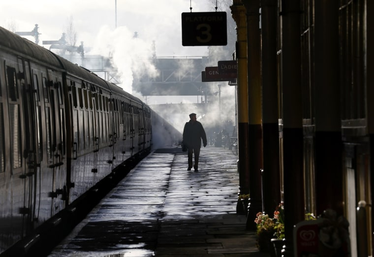 Image: A man walks past the carriages pulled by The Flying Scotsman steam engine at East Lancashire Railway in Bury