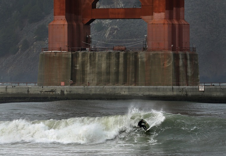 Image: A surfer rides a wave underneath the south tower of the Golden Gate Bridge