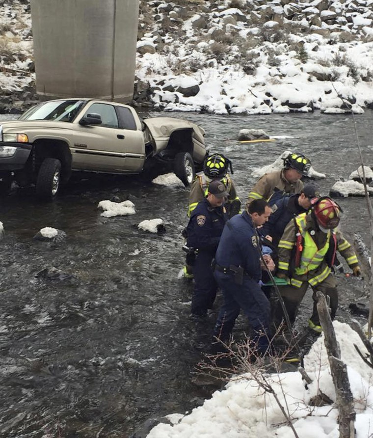 Image: Fire rescue and California Highway Patrol members carry away a man whose truck slid off Interstate 80