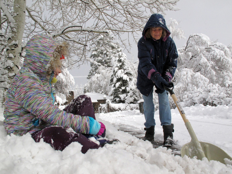 Image: A woman shovels snow from the sidewalk outside her homes
