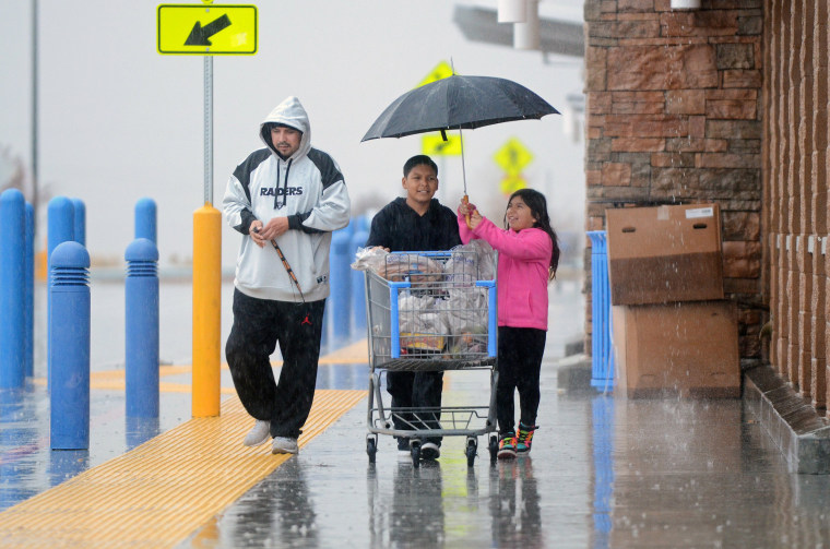 Image: A girl takes tries to cover a shopping cart from rain at Walmart in Hesperia, Calif.