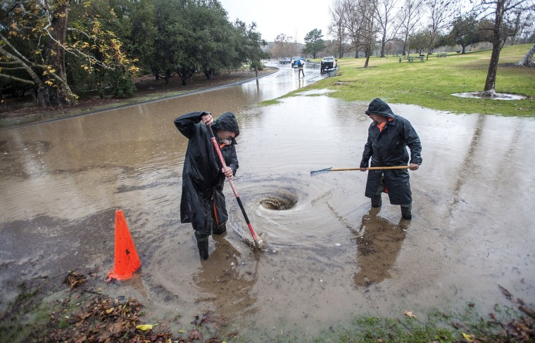 Image: Crews clean out debris from a block drain at Irvine Regional Park in Orange, Calif.