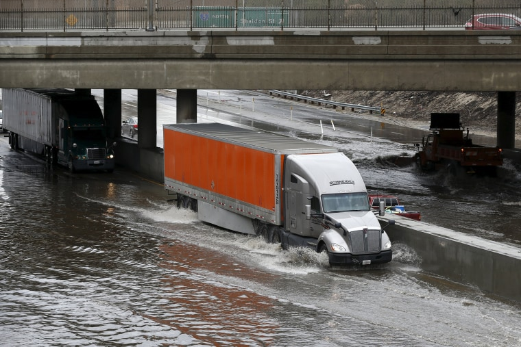 Image: Trucks drive on the flooded 5 freeway after an El Nino-strengthened storm brought rain to Los Angeles