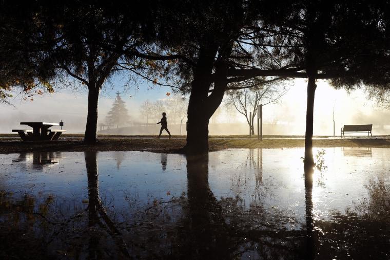 Image: A walker takes advantage of the clearing skies to stroll past rain puddles at Lake Balboa Park