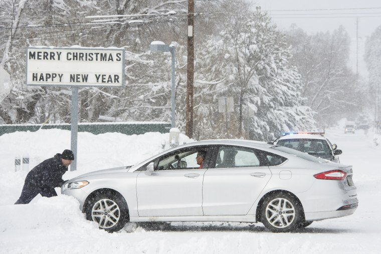 Image: Flagstaff resident Anthony Martinez pushes a motorist out of the snow