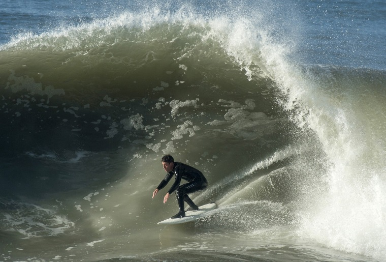 Image: A surfer rides a wave in Seal Beach, Calif.
