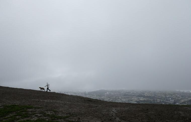 Image: A man walks a dog under rain clouds atop Bernal Heights Hill in San Francisco
