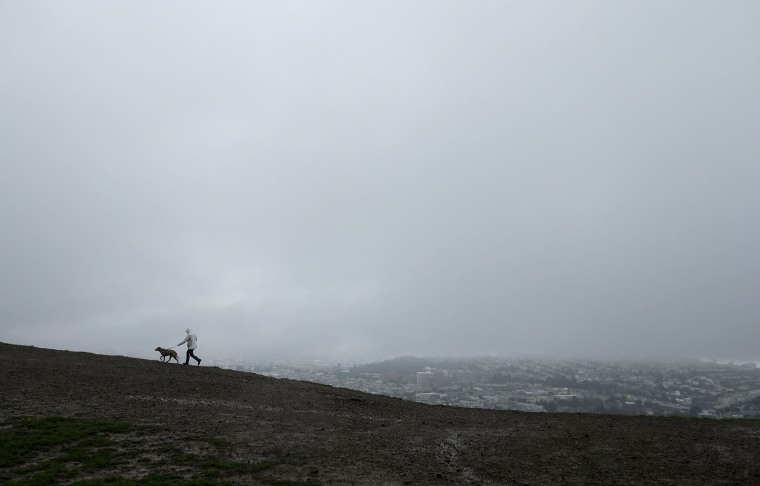 Image: A man walks a dog under rain clouds atop Bernal Heights Hill in San Francisco