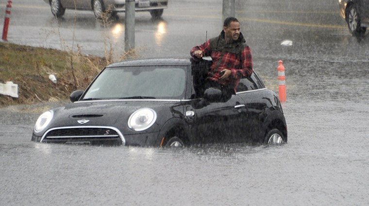 Image: A driver climbs out of a window of his car after driving onto a flooded road in Van Nuys