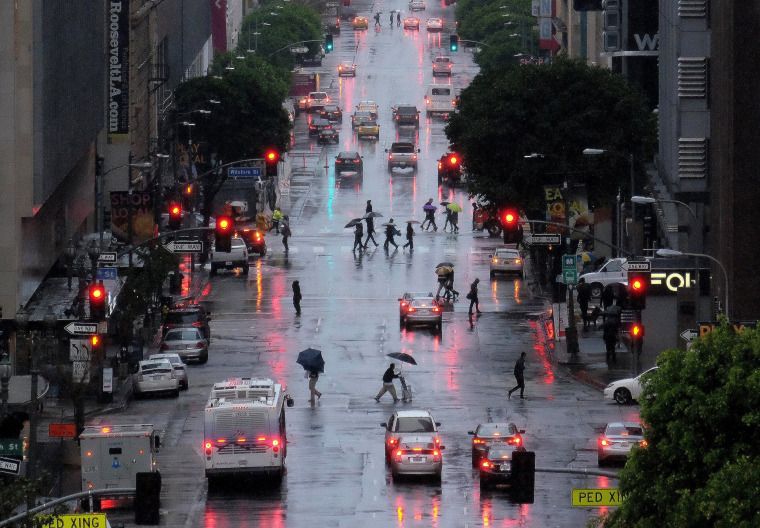Image: Pedestrians, cover up from heavy El Nino rains, cross Flower Street in downtown Los Angeles