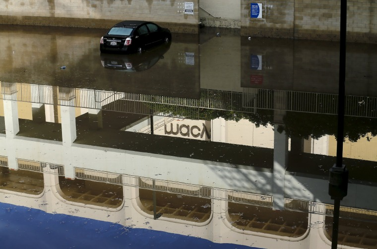 Image: An abandoned car sits in flood waters at a local shopping mall after El Nino-strengthened storm brought rain to San Diego