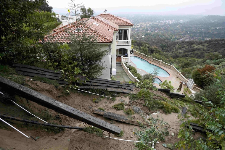 Image: A home with a fence destroyed by a mudslide is seen after El Nino-strengthened storm brought rain to Pasadena