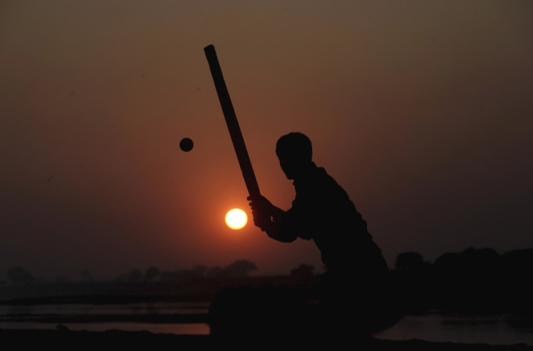Image: A man is silhouetted against the setting sun as he plays cricket near the banks of the Ravi river in Lahore