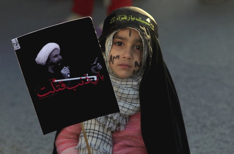 Image: A Shi'ite Muslim girl holds a picture of Shi'ite Muslim cleric Nimr al-Nimr as she takes part in a protest rally in Islamabad