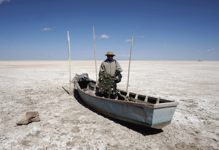 Image: Fisherman Rene Valero, from the Urus ethnic group, is seen on his boat on the dried Poopo lakebed in the Oruro Department, south of La Paz, Bolivia