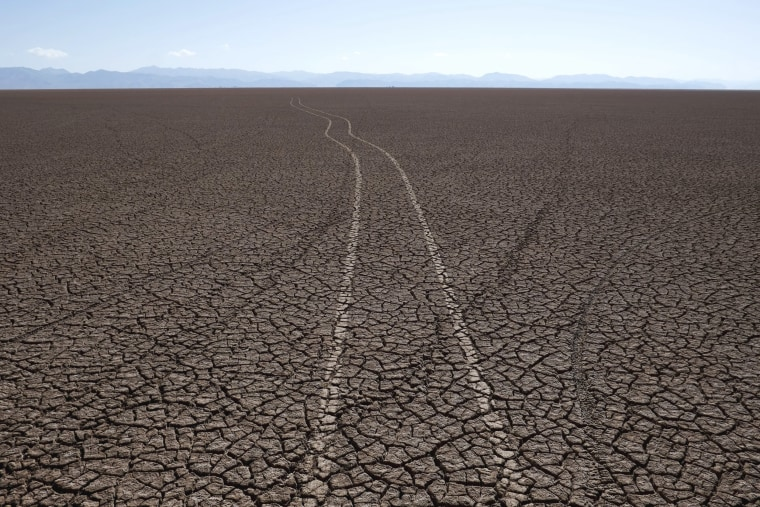 Image: Marks of car tires are seen on the dried Poopo lakebed in the Oruro Department, south of La Paz, Bolivia