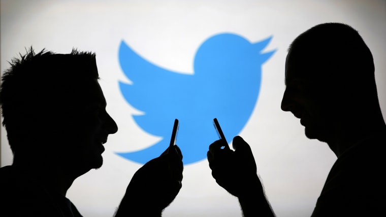 Image: Men are silhouetted against a video screen with an Twitter logo as he poses with an Samsung S4 smartphone in this photo illustration taken in the central Bosnian town of Zenica