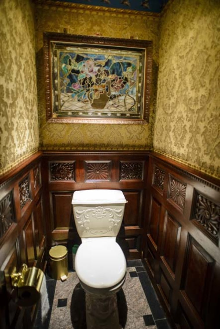 A Tiffany-stained glass sits above a toilet.