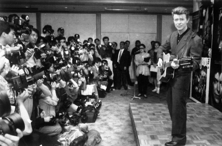 Image: Bowie plays an acoustic guitar at a press conference in Tokyo on May 19, 1990.