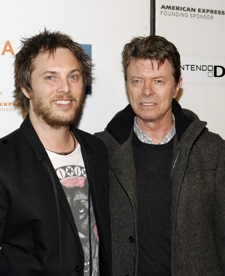 Image: Director Duncan Jones, left, and his father David Bowie arrive at a movie premiere on April 2009