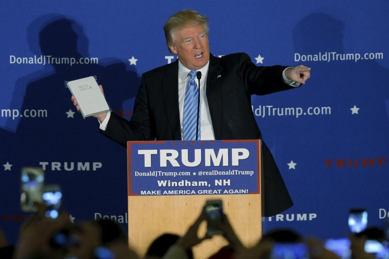 Image: U.S. Republican presidential candidate Donald Trump holds a Bible given to him by an audience member at a campaign rally in Windham