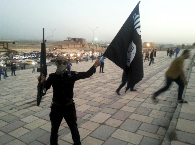 Image: File photo of a fighter of ISIL holding a flag and a weapon on a street in Mosul