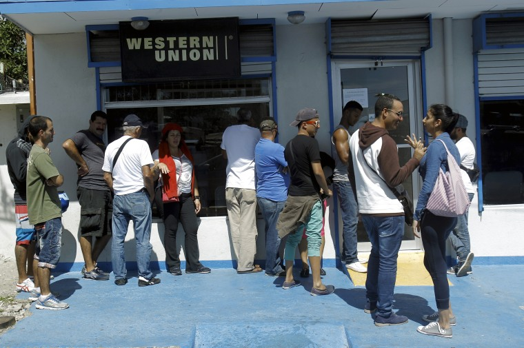 Image: Cuban migrants line up while waiting outside Western Union branch in the town of La Cruz, Costa Rica