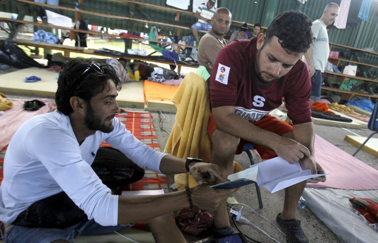 Image: Cuban migrant Ivan Tamayo shows his compatriot Dany Cejas a document which will allow migrants to continue their journey to the Guatemala-Mexico border, at a shelter in La Cruz
