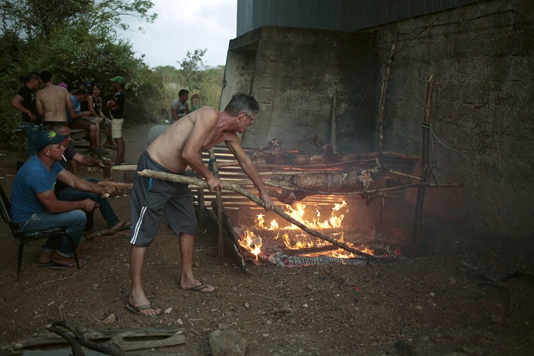 Image: Cuban migrants prepare pigs for Christmas eve dinner in the town of La Cruz